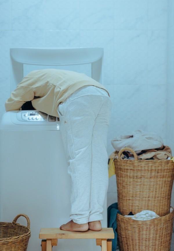 personne qui met la tête dans une machine à laver