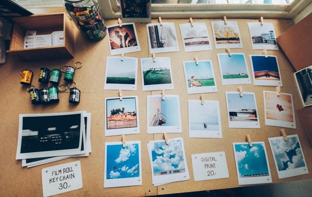 Nombreuses photographies Polaroid étalées sur une table en bois