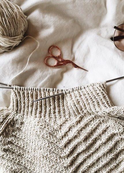 pull en laine avec des aiguilles, une paire de ciseaux et du fil