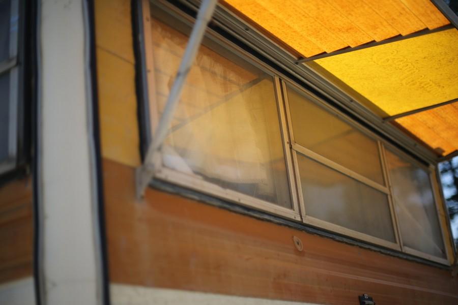fenêtre d'un mobil home sous un auvent