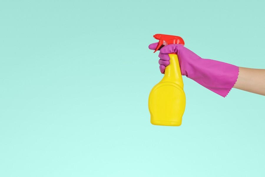 main avec un gant qui tient un pulvérisateur pour nettoyer