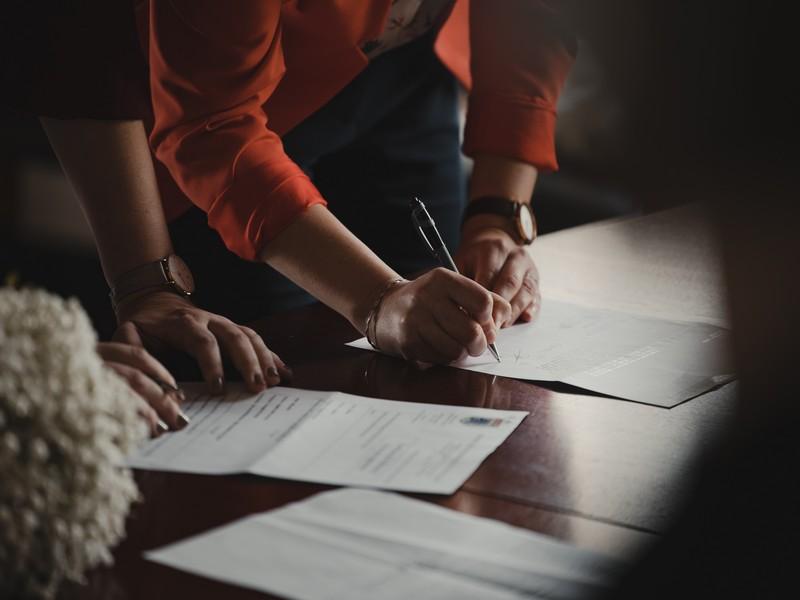 personnes en train de signer des contrats