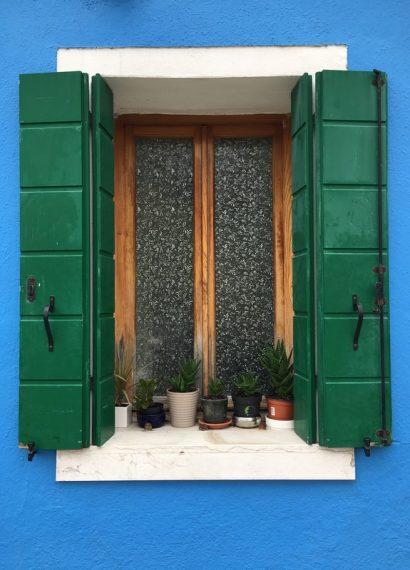 volets verts d'une maison à la façade bleue