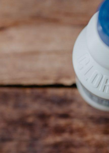 bouteille de javel posée sur un meuble en bois