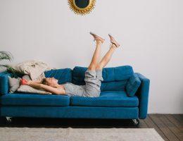 femme allongée sur un canapé bleu canard qui lève les jambes au ciel