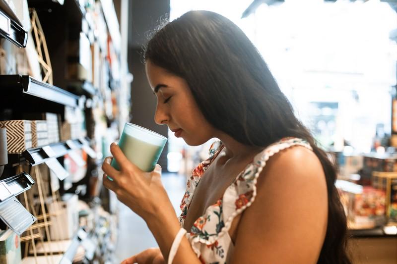 femme qui sent une bougie dans une boutique