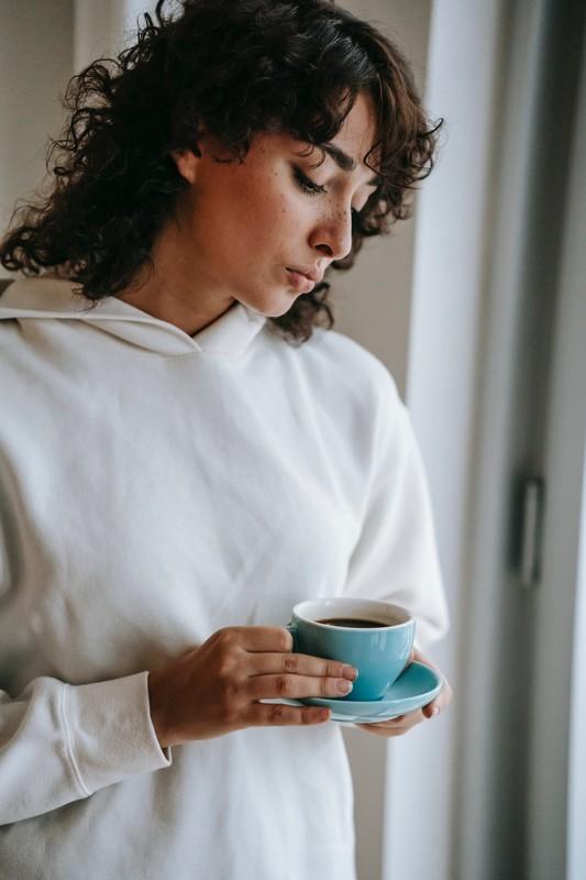 femme triste devant une fenêtre qui tient une tasse de café