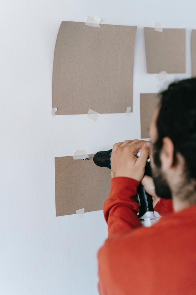 homme qui fait des essais sur son mur pour placer des cadres de couleurs