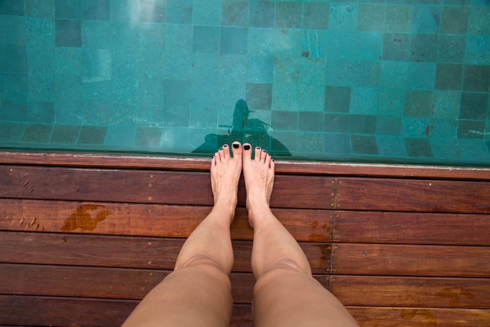 jambes d'une femme sur la terrasse d'une piscine hors sol
