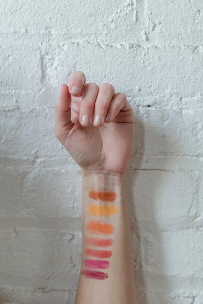 main devant un mur de brique avec des tests de couleurs sur l'avant bras