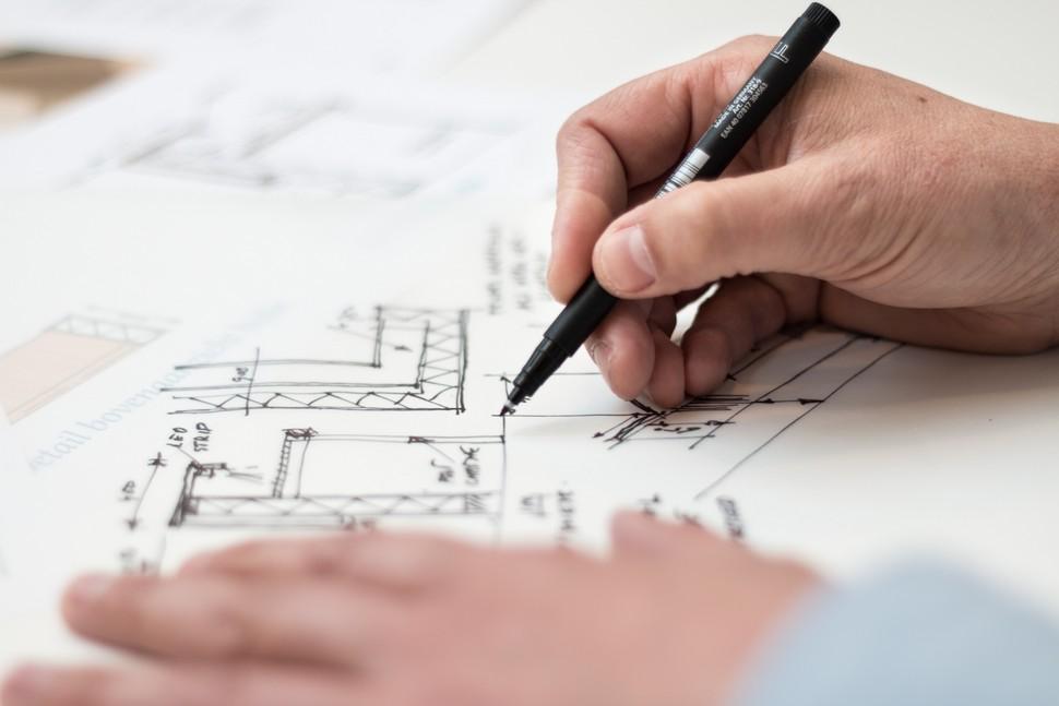mains d'une personne qui dessinent un plan