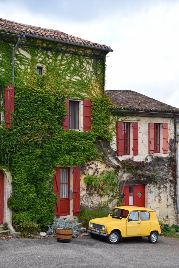 maison traditionnelle avec du liere sur la façade et les volets rouges