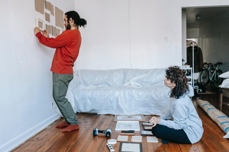 couple qui fait des essais pour disposer des cadres au mur